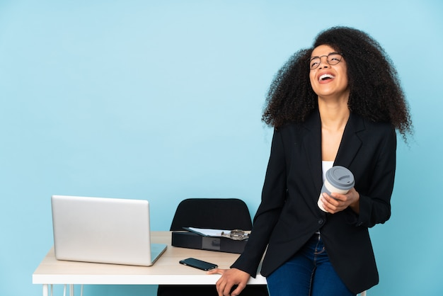 Afro-amerikaanse zakenvrouw werken op haar werkplek poseren met armen op heup en glimlachen