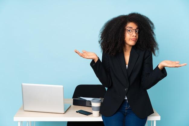 Afro-amerikaanse zakenvrouw werken op haar werkplek twijfels gebaar maken