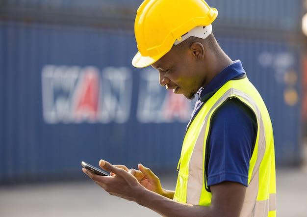 Afro-amerikaanse zwarte mannen werknemers spelen, online chatten of browsen op de mobiele telefoon terwijl ze een pauze nemen op de bouwplaats