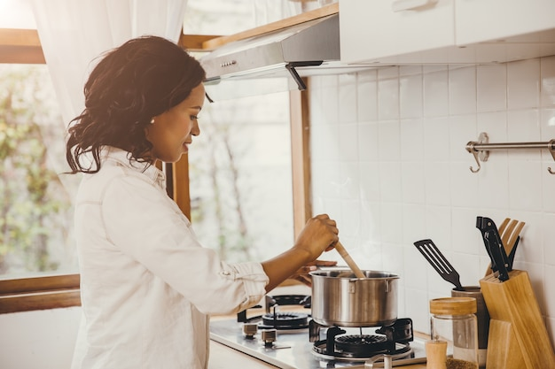 Afro-amerikaanse zwarte vrouw koken kokende soep in de keuken thuis.