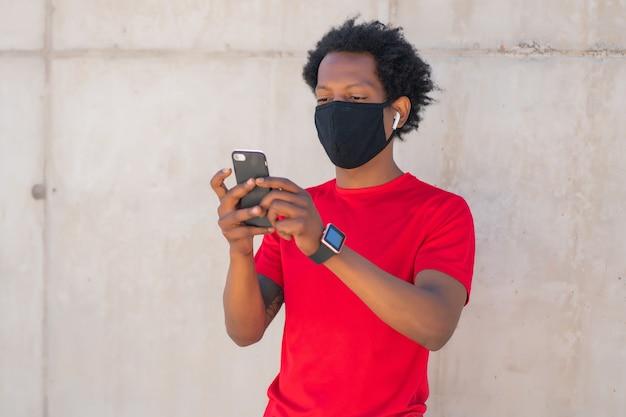 Afro-atletische man die een gezichtsmasker draagt en zijn mobiele telefoon gebruikt na het sporten in de buitenlucht. sport en technologie concept. nieuwe normale levensstijl.