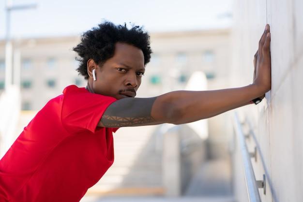 Afro atletische man die zich uitstrekt en opwarmt voordat hij buiten gaat trainen. sport en een gezonde levensstijl.