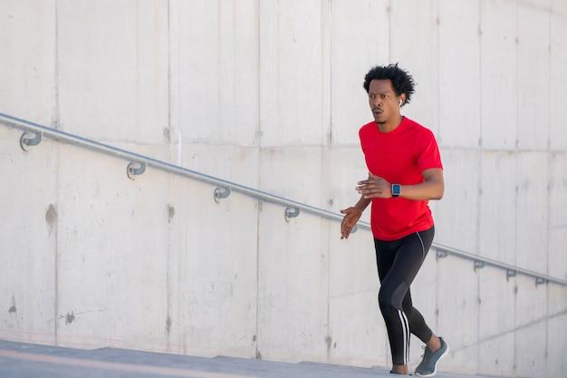 Afro atletische man doet oefeningen en rent buiten de trap op
