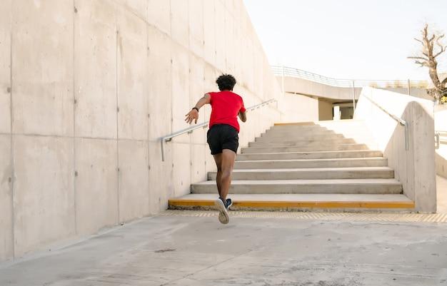 Afro atletische man loopt en doet oefening buitenshuis