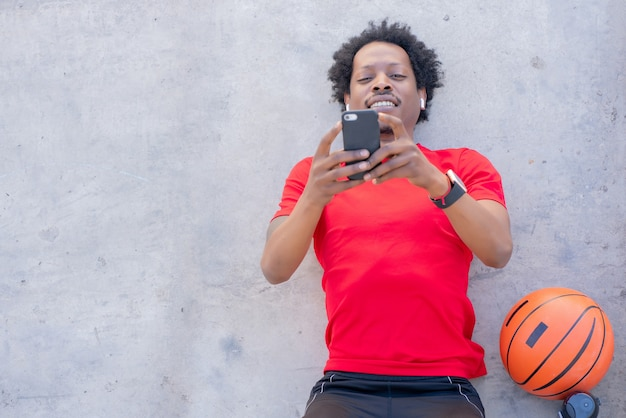 Afro atletische man met behulp van zijn mobiele telefoon en ontspannen na de training buitenshuis.