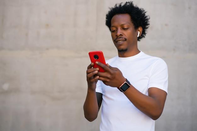 Afro atletische man met behulp van zijn mobiele telefoon en ontspannen na de training buitenshuis