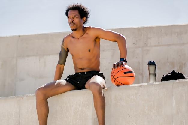 Afro atletische man met een basketbalbal en ontspannen na de training buitenshuis. sport en een gezonde levensstijl concept.