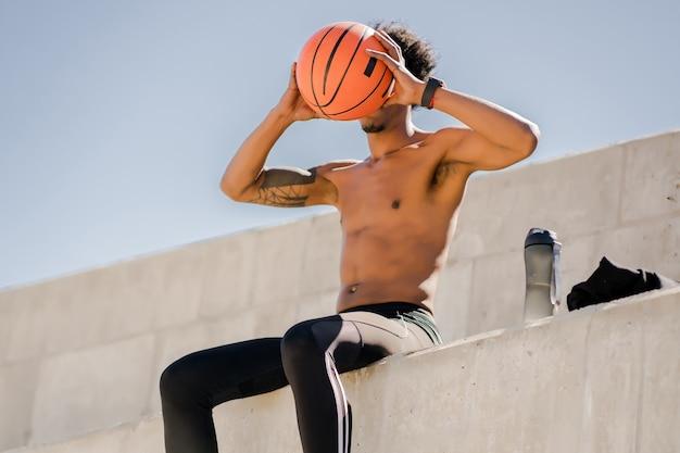 Afro atletische man met een basketbalbal en ontspannen na de training buitenshuis.
