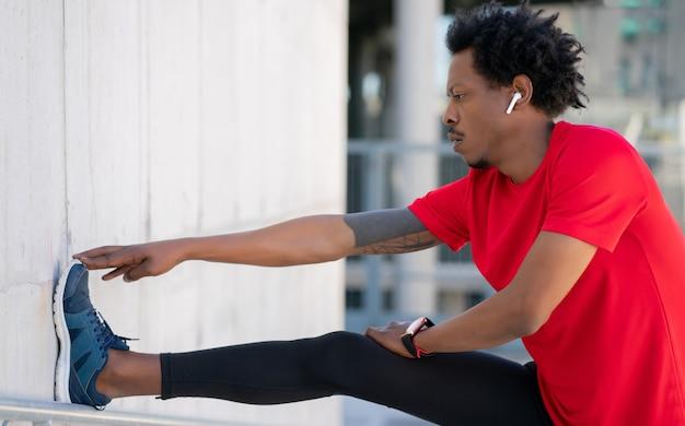 Afro atletische man zijn benen strekken en warming-up voor het sporten buiten. sport en een gezonde levensstijl concept.