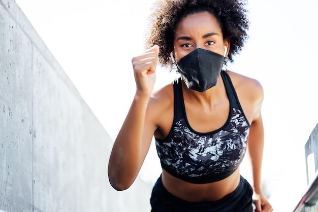 Afro atletische vrouw die gezichtsmasker draagt tijdens het buiten hardlopen. nieuwe normale levensstijl. sport en een gezonde levensstijl concept.