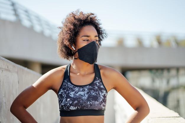 Afro atletische vrouw gezichtsmasker dragen en ontspannen na het trainen buiten op straat. nieuwe normale levensstijl. sport en een gezonde levensstijl.
