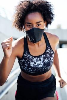 Afro atletische vrouw gezichtsmasker dragen tijdens het buiten hardlopen