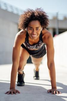Afro atletische vrouw klaar om buiten te rennen