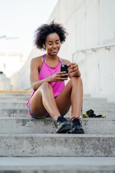 Afro atletische vrouw met behulp van haar mobiele telefoon en ontspannen na de training buitenshuis. sport en technologie concept.