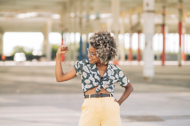 Afro-blonde vrouw, bril, lesgeven in spieren, krachtige vrouw