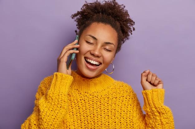 Afro-dame heeft telefoongesprek, heeft grappig, grappig gepraat, steekt gebalde vuist op, glimlacht in grote lijnen geïsoleerd op paarse achtergrond
