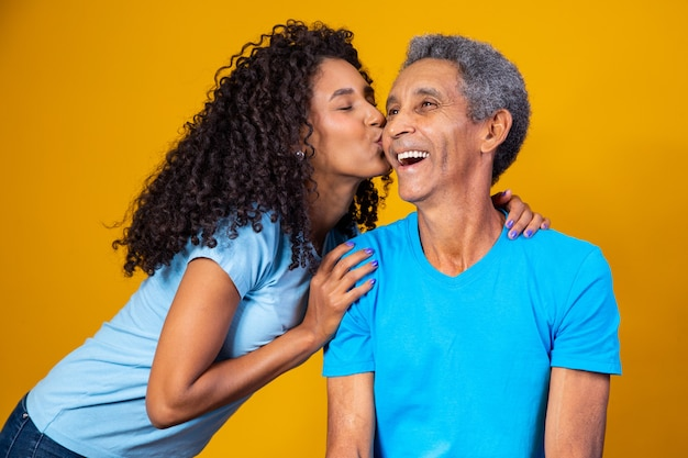 Afro-dochter die de wang van haar oudere vader kust. vaderdag concept