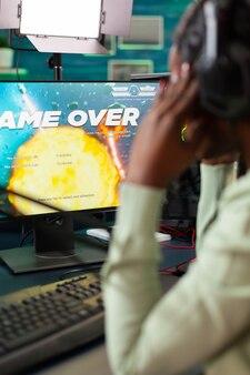 Afro-esportspeler die een nederlaag lijdt tijdens space shooter live-toernooi. professionele gamer die online videogames streamt met nieuwe graphics op een krachtige computer.