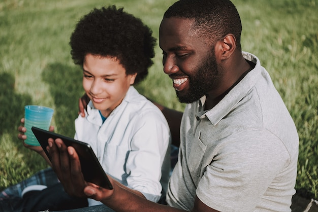 Afro father hugs son op picnic and boy show op tablet