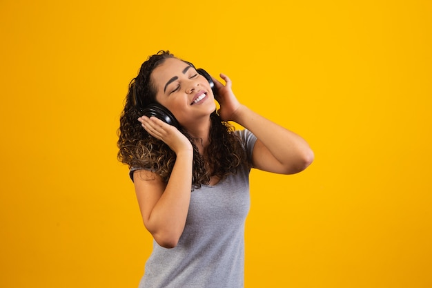 Afro jong meisje met haar koptelefoon luisteren naar muziek