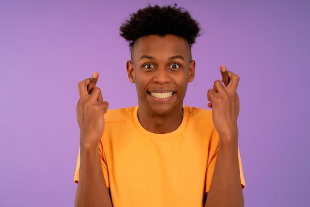 Afro jonge man die haar vingers kruist en veel geluk wenst.