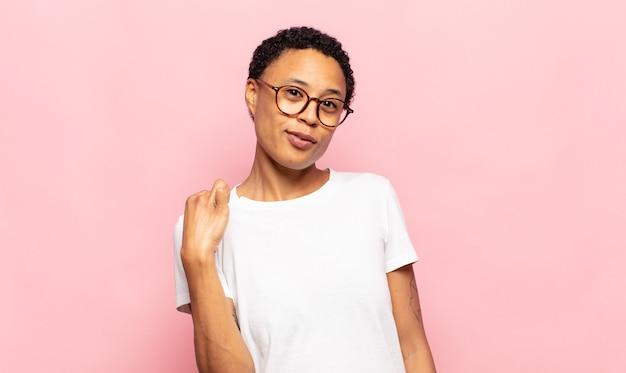 Afro jonge vrouw die er arrogant, succesvol, positief en trots uitziet, wijzend naar zichzelf
