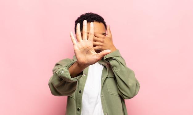 Afro jonge vrouw die gezicht bedekt met hand en andere hand naar voren zet om de camera te stoppen, foto's of afbeeldingen weigeren