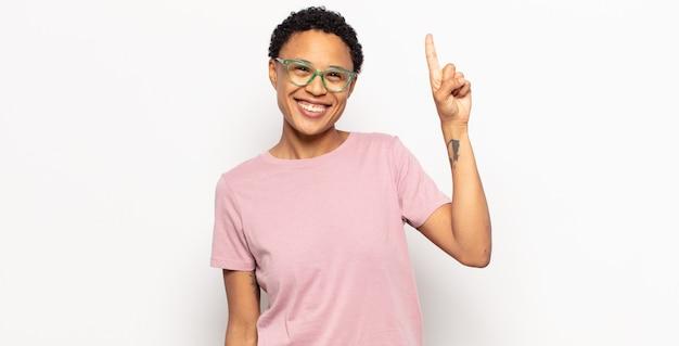 Afro jonge vrouw die vrolijk en gelukkig lacht, met één hand naar boven gericht om ruimte te kopiëren