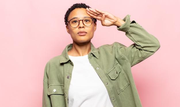 Afro jonge zwarte vrouw die de camera begroet met een militaire groet in een daad van eer en patriottisme, respect tonen