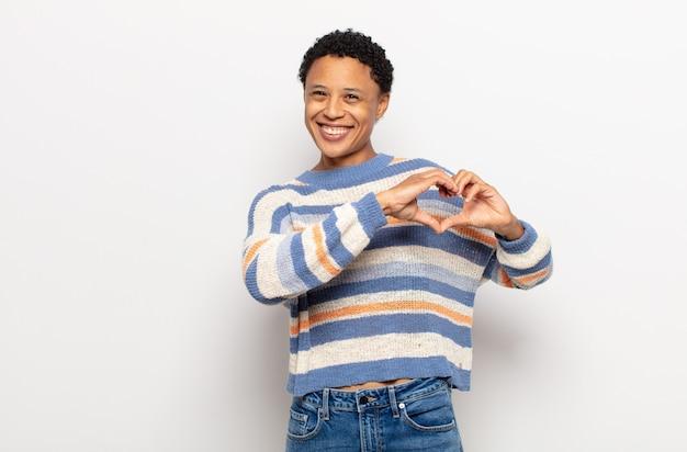 Afro jonge zwarte vrouw die lacht en zich gelukkig, schattig, romantisch en verliefd voelt, hartvorm met beide handen maakt