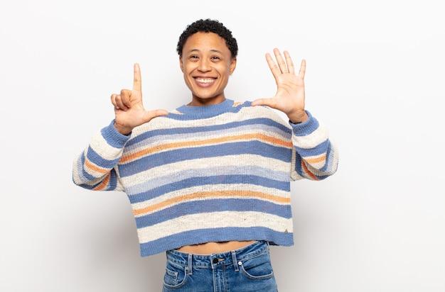 Afro jonge zwarte vrouw die vriendelijk glimlacht en kijkt, nummer zeven of zevende met vooruit hand toont, aftellend
