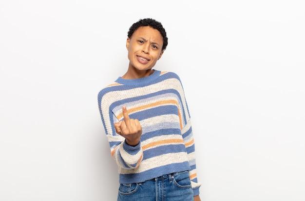 Afro jonge zwarte vrouw die zich boos, geïrriteerd, rebels en agressief voelt, de middelvinger wegknipt, terugvecht