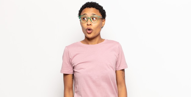 Afro jonge zwarte vrouw die zich geschokt, blij, verbaasd en verrast voelt, opzij kijkend met open mond