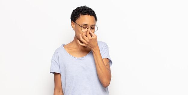 Afro jonge zwarte vrouw die zich gestrest, ongelukkig en gefrustreerd voelt, het voorhoofd aanraakt en lijdt aan migraine of ernstige hoofdpijn