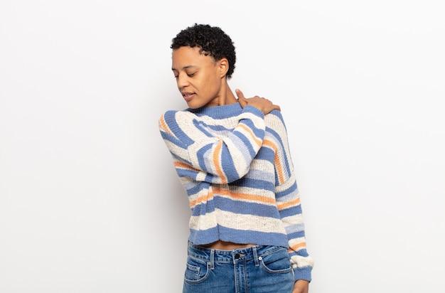 Afro jonge zwarte vrouw die zich moe, gestrest, angstig, gefrustreerd en depressief voelt, rug- of nekpijn heeft