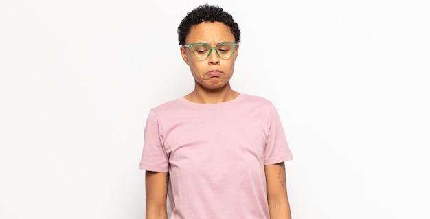 Afro jonge zwarte vrouw die zich verdrietig en gestrest voelt, overstuur vanwege een onaangename verrassing, met een negatieve, angstige blik