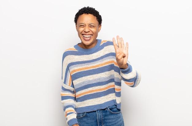 Afro jonge zwarte vrouw lacht en ziet er vriendelijk uit, toont nummer vier of vierde met de hand naar voren, aftellend