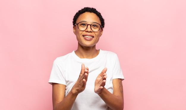 Afro jonge zwarte vrouw voelt zich gelukkig en succesvol, lacht en klapt in de handen, zegt gefeliciteerd met een applaus