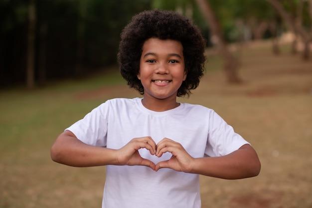 Afro-jongen die hart maakt met zijn hand