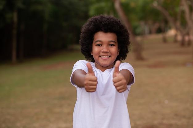 Afro jongen met duim omhoog met ruimte voor tekst op de achtergrond van de natuur.
