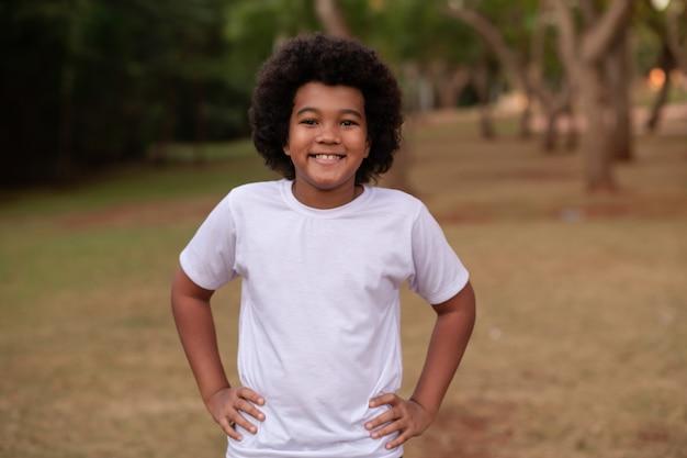 Afro jongen ontspannen in het park glimlachend