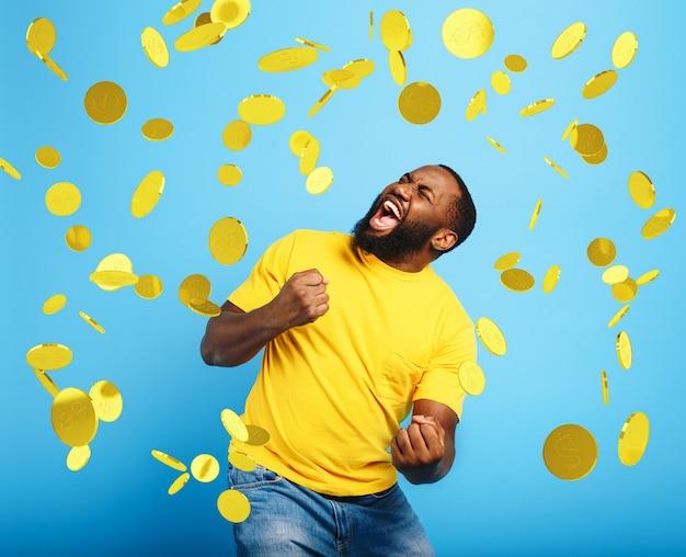 Afro jongen wint geld. verbaasd en verbaasd gezicht. lichtblauwe muur