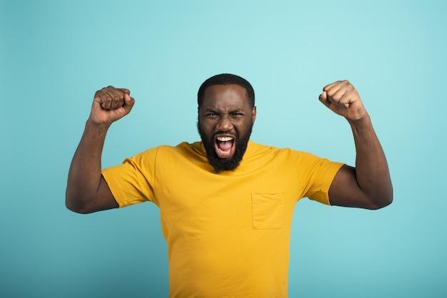 Afro-jongen wint iets. verbaasd en verbaasd gezicht. lichtblauwe muur