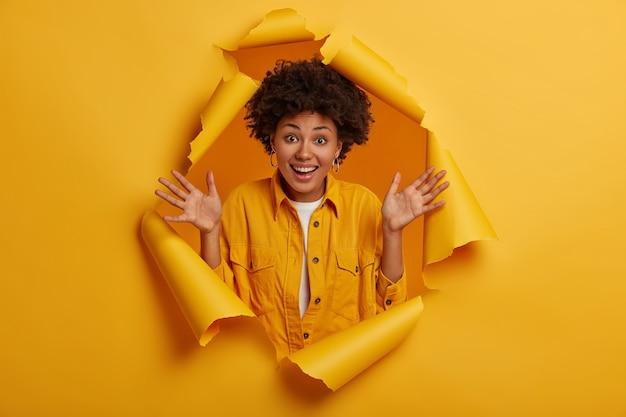 Afro-kapsel houdt de handpalmen omhoog, geniet van aangenaam nieuws, heeft natuurlijk krullend haar, toont opwinding en geluk, staat in een gescheurd gat van een gele papieren muur