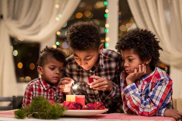 Afro-kinderen steken kerstkaarsen aan, jongens steken kaarsen aan tijdens de voorbereidingen voor de kerstvakantie in de...