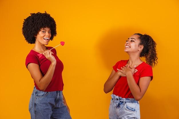 Afro lesbisch koppel op geel. homo-affectieve koppel