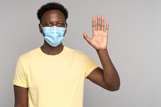Afro-man draagt een beschermend gezichtsmasker om te beschermen tegen coronavirus covid-19 met stijgende palm omhoog geïsoleerd