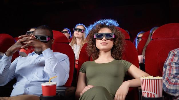 Afro man en gekrulde brunette zitten in de bioscoop