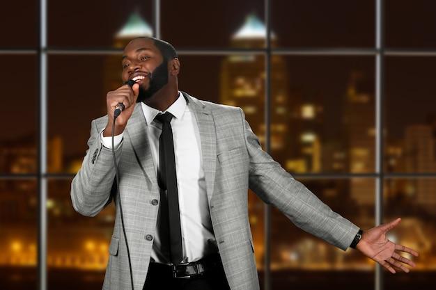 Afro man met microfoon zingen.