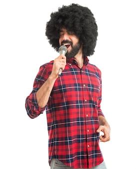 Afro man zingen met een microfoon